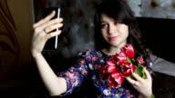 Beautiful brunette girl doing selfie with red flowers tulips on black smatfon. video