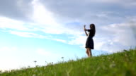 Beautiful brunette girl in black dress standing on grassy hill and making photos with her phone. FullHD video video