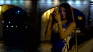 Beautiful brunette girl in dress standing on evening urban embankment and making photos with her mobile phone. FullHD video video