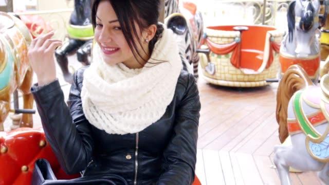 Beautiful brunette girl riding on carousel video