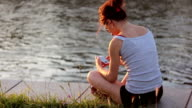 Beautiful brunette girl siting on the shore of the river with the phone, typing the message. Soft sunlight, hot, sunny autumn day. video