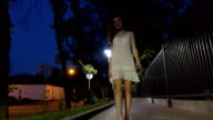 Beautiful brunette girl walking at camera on night street steadicam FullHD shot video