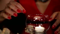 Beautiful Brunette in Red Dress Playing with a Candle and Melting Ice Cubes on the Mirror Table video
