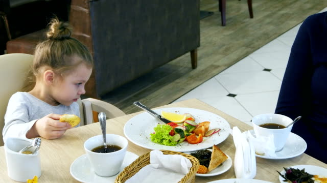 Beautiful brunette mother persuading her young blond daughter to eat vegetable salad in cafe video