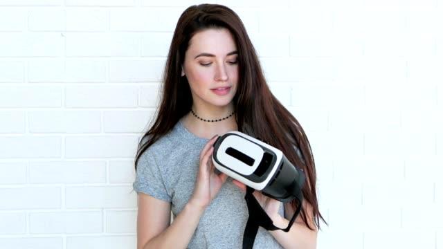 Beautiful brunette puts on virtual reality glasses. video