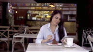 Beautiful brunette social networking on her smartphone while enjoying a cake video