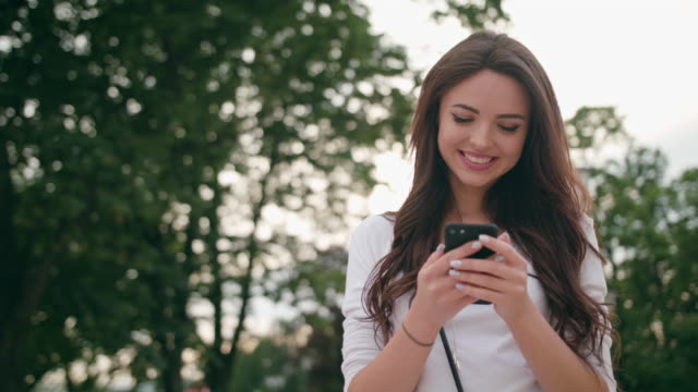 A Beautiful Brunette Using a Mobile Phone Outdoors video