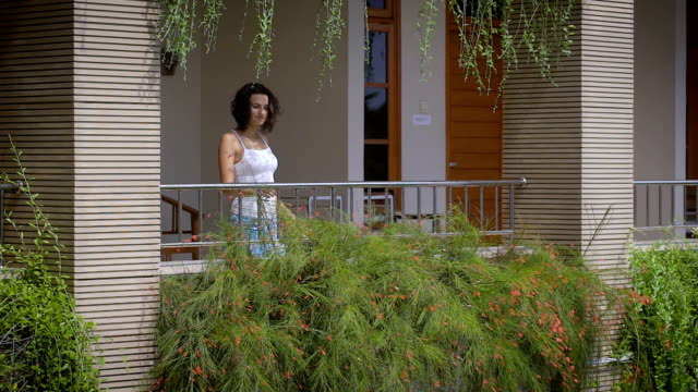Beautiful brunette walking out on balcony of her tropical private villa and breathing in fresh Balinese air. Young female traveler enjoying her vacation on terrace among tropical luxuriant vegetation video