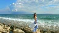 Beautiful brunette woman in maxi dress enjoying windy day on seashore, vacation video