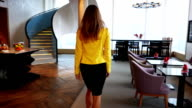 beautiful business woman in yellow jacket goes to the window at modern building video