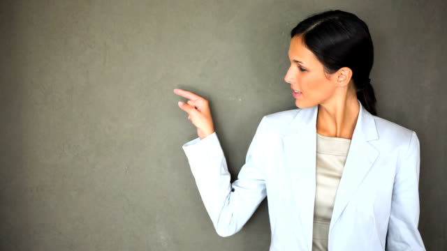 Beautiful businesswoman pointing at copy space video