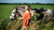 A beautiful charming blonde woman walking with a horse at a field video