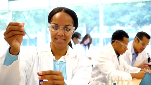 Beautiful chemistry student or chemist drops liquid into test tube video