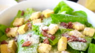 Beautiful colourful caesar salad with dressing croutons and parmesan cheese together with yellow pumpkin soup. healthy meal video