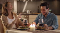 Beautiful Couple Having Candlelight Dinner in the Kitchen. They Eat, Drink and Talk. Both are in Good Mood and Smile a lot. Slow Motion. video