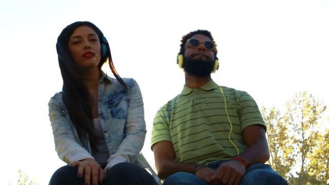 Beautiful couple listening to music with headphones on sunny day video
