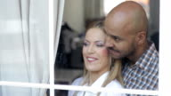 Beautiful couple looking through window video
