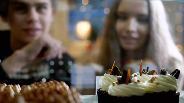 Beautiful couple of young people in a candy store. A girl and a guy in a sweater choose Cake and desserts for themselves. Showcase pleasantly decorated. The girl with long hair, brunette video