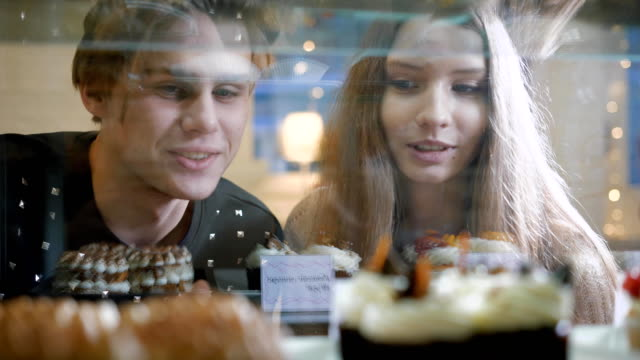 Beautiful couple of young people in a candy store. The girl and the guy chosen Cake and desserts for themselves. Showcase pleasantly decorated video