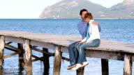 beautiful couple sitting on the jetty enjoying the day video