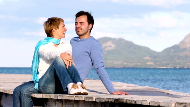 beautiful couple sitting on the jetty enjoying the sea video