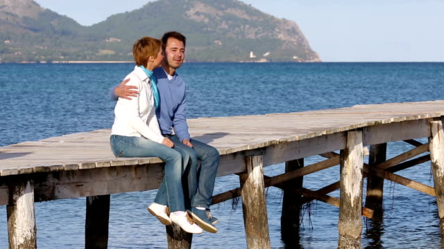 beautiful couple sitting on the jetty enjoying their time video