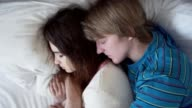 Beautiful couple sleeping together in the bed. The man is embracing the woman video