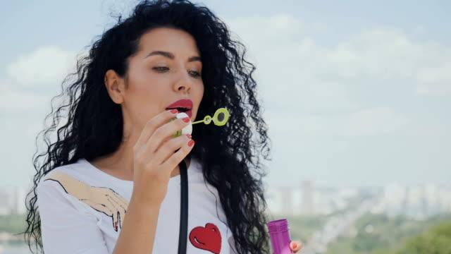 Beautiful curly brunette blows bubbles video
