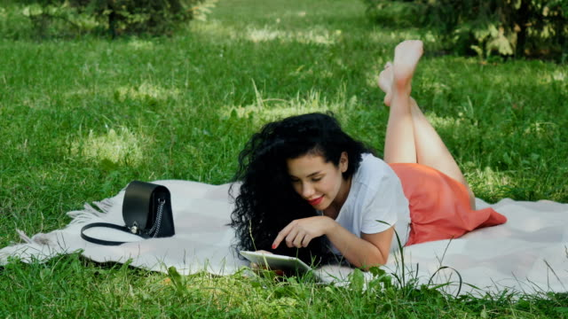 Beautiful curly girl relax on plaid in park on green grass video