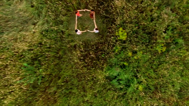 beautiful dancing girl in the field - the evening dance in a circle - aerial video
