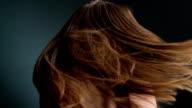 Beautiful dark blond woman flipping long hair video