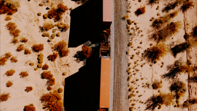 A beautiful drone shot tracking up as the camera looks down on a passing container train in the desert. video
