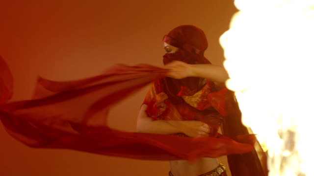 Beautiful Ethnic Asian Dance. Dancing with fire on red background. Slow Motion, video