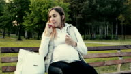 Beautiful expectant mother lipstick in a park. video
