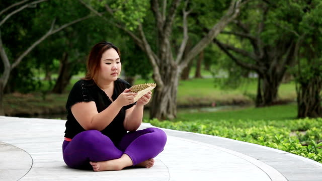 Beautiful fat woman picks up smelling durian, and put it down. video