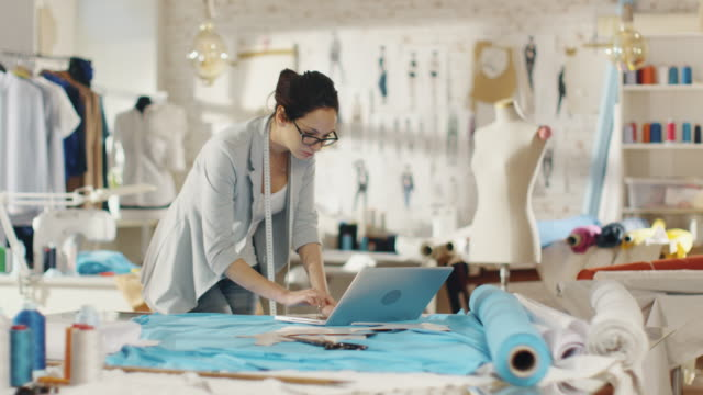 Beautiful Female Designer Uses Laptop on Her Desk that is Covered with Various Fabrics and Sewing Items. Her Studio is Sunny, There is Mannequin, Clothes Hanging and Sketches Pinned to the Wall. video