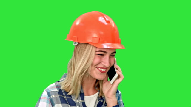 Beautiful female engineer in hardhat calling via cellphone on a Green Screen, Chroma Key video