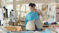 Beautiful Female Fashion Designer Adjusting Fabrics on a Tailored Mannequin. In Her Studio Various Sewing Items and Colourful Fabrics Laying around, Mannequins Standing, and Sketches Pinned. video