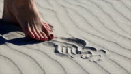 Beautiful female legs playing with sand on the sandy sea beach video