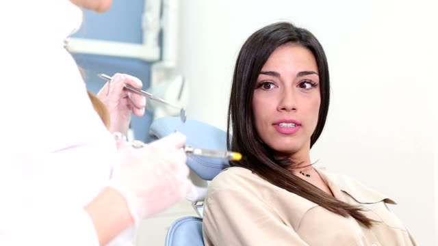 Beautiful female patient faking fear of injection at dentist video