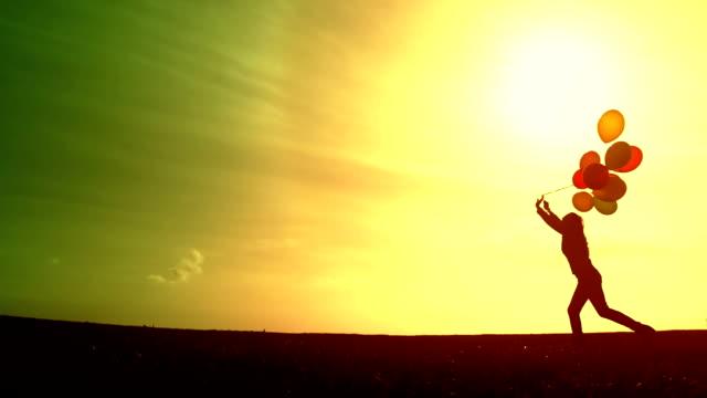 Beautiful female Silhouette Running Free Balloons video