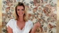Beautiful flirting blonde woman smiling at camera video
