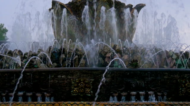Beautiful fountain in the city park. The sun illuminates the splashes of water. Shining splash of water. video