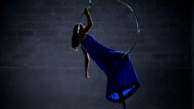 Beautiful gentle girl in blue long dress spins in the aerial hoop video