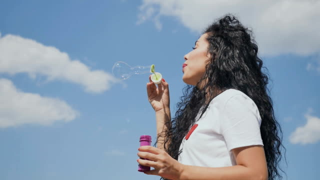 Beautiful girl blows bubbles at sky background video