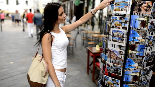 Beautiful girl choosing from postcard stand on the street. video