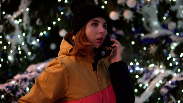 Beautiful Girl dialing a number, Talking with Friend at the christmas tree background in the evening. video