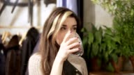 Beautiful Girl Drinking Cacao or Coffee in Cafe. Beauty Model Woman with the Cup of Hot Beverage. Spruce's branches at the background video