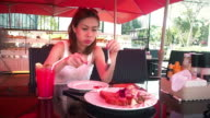Beautiful girl eating delicious grilled steak in restaurant video
