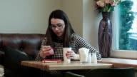 beautiful girl enjoying an hot coffee in cafe with window video